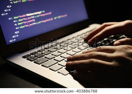 Hacker using laptop, closeup - stock photo