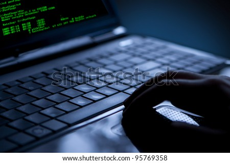 Hacker using laptop. Lots of digits on the computer screen. - stock photo