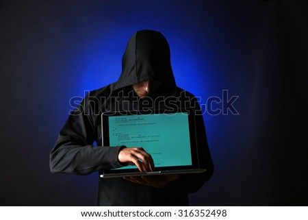 Hacker with computer and laptop on colorful dark background  - stock photo