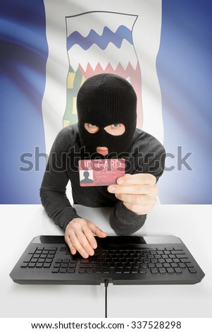 Hacker with ID card in hand and Canadian province flag on background - Northwest Territories - stock photo