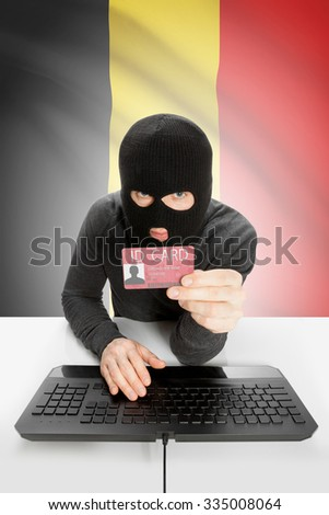 Hacker with ID card in hand and flag on background - Belgium - stock photo