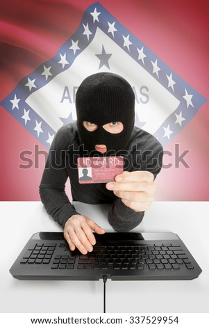 Hacker with ID card in hand and USA states flag on background - Arkansas - stock photo