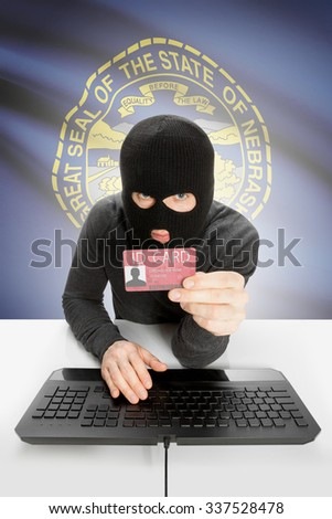 Hacker with ID card in hand and USA states flag on background - Nebraska - stock photo