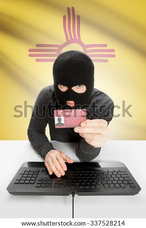 Hacker with ID card in hand and USA states flag on background - New Mexico - stock photo