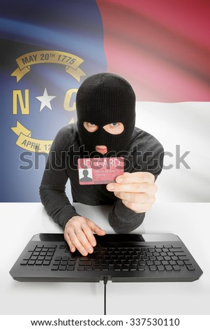 Hacker with ID card in hand and USA states flag on background - North Carolina - stock photo
