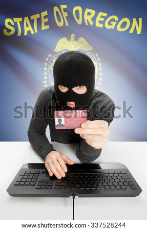 Hacker with ID card in hand and USA states flag on background - Oregon - stock photo