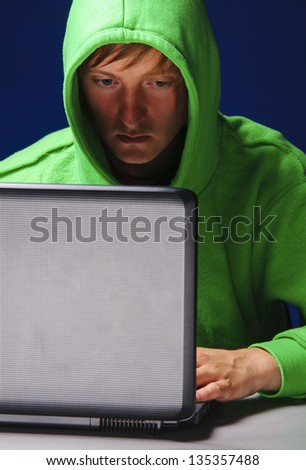 hacker. Young man with laptop is looking at screen