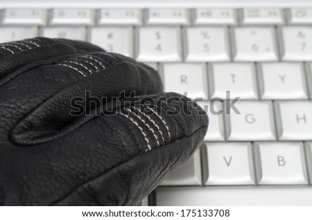 Hacking concept with hand in black leather glove over the laptop keyboard - stock photo