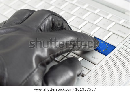 Hacking Europe concept with hand wearing black leather glove pressing enter key with flag overlaid