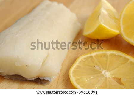 Haddock fillet and lemon segments on a wooden chopping board