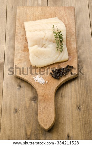 haddock fillet with thyme, coarse salt and pepper on a wooden board - stock photo