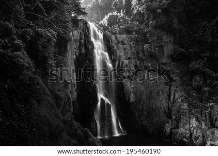 Haew Narok (chasm of hell) waterfall, Kao Yai national park, Thailand with a man beside compare size in black and white - stock photo