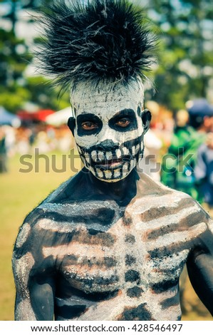 Hagen show, Papua New Guinea - circa August 2015: Native man with black and white colour on his body in form of skeleton wears fur cap during Hagen show, Papua New Guinea. Documentary editorial.
