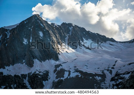Hagerman's Peak in the Elk Mountain Range with its Large massive Glacier Snowmass sitting to the right with a large cloud coming over the ridge near Aspen , Colorado Rocky Mountain Landscape