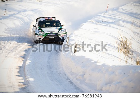 HAGFORS, SWEDEN - FEB 10: Mads Ostberg drivning his Ford Fiesta RS during the World Rally Championship event Rally Sweden in Hagfors, Sweden on Feb 10, 2011 - stock photo