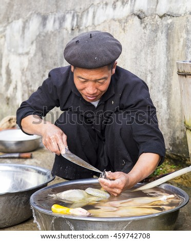 Hagiang, Vietnam - Apr 16, 2016: Vietnamese man washing and cleaning dead chicken for sale in Vietnam