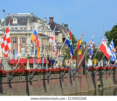 HAGUE, NETHERLANDS-AUGUST 01, 2014: Historical centre of Hague near lake Hofvijver with flags of provinces, Netherlands. This is one of mostly popular visiting sites for tourists in the city - stock photo