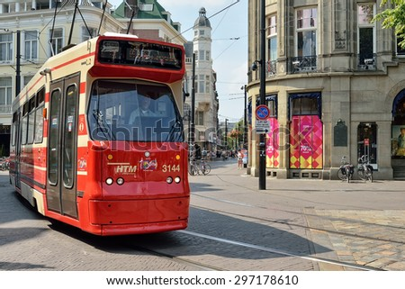 HAGUE, NETHERLANDS-AUGUST 01, 2014: Red tram moves by street in historical center of Hague.
