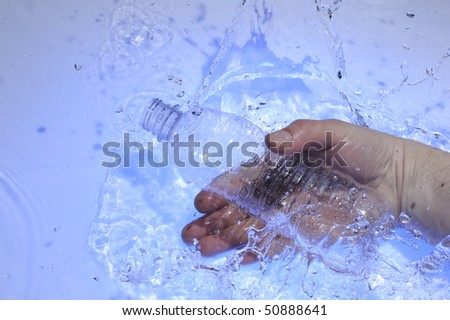 Hahd with plastic bottle in blue water
