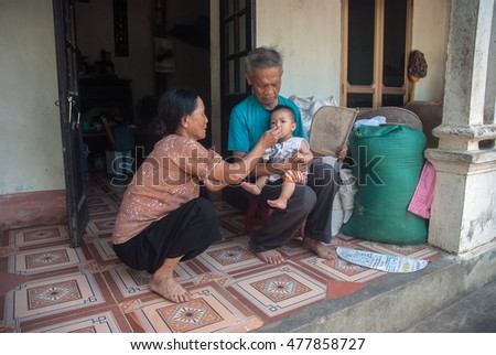 HAI DUONG, Vietnam, August 26, 2016 grandparents, care, young nephew, a suburb of Hai Duong, Vietnam. their simple happiness