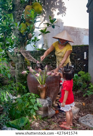 HAI DUONG, Vietnam, May 28, 2016 the mother and daughter, countryside Hai Duong, vases lotus care
