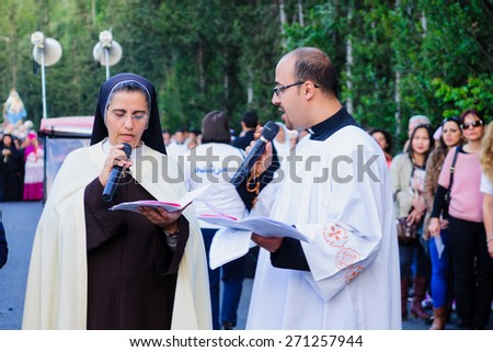 HAIFA, ISRAEL - APR 19, 2015: Local nun and priest in a prayer to Mary, as part of the annual our lady of Mount Carmel parade, Haifa, Israel. This event commemorates the hiding of Mary statue in WWI - stock photo