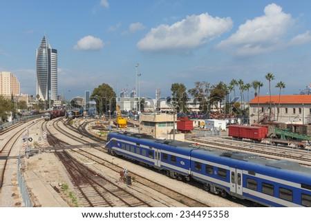 Haifa, Israel - December 1, 2014: View of Haifa's downtown area with railroads, train and urban landscape under blue sky. - stock photo