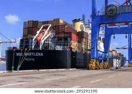 Haifa, Israel - July 10, 2015: Haifa's Port dock with container ship and Various brands and colors of shipping containers stacked in a holding platform waiting for loading.