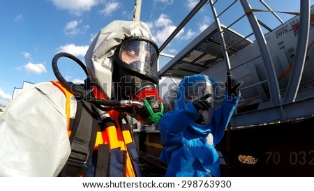 HAIFA, ISRAEL - JUNE 30, 2015: Firefighters from Northern Israel with protective gear talk with hands during simulation drill of leak of Bromine chemical in a container car of train.