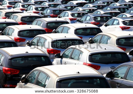 Haifa, Israel - October 16, 2015: Rows of new cars covered in protective white sheet parked in Haifa's port platform - stock photo