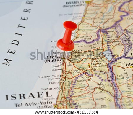 Haifa marked on map with red pushpin. Selective focus on the word Haifa and the pushpin. Pin is in an angle. Midground is sharp while foreground and background is blurry. - stock photo