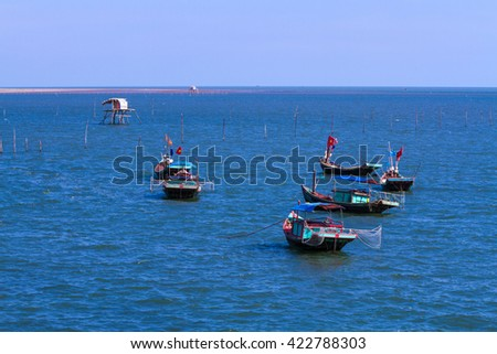 HAIHAU, VIET NAM- AUGUST 27: Fishing village with wooden boat berth at seashore and coracle float on water in Hai Hau, Viet Nam on August 27, 2013