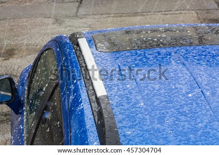 Hail falls on a blue car roof. - stock photo