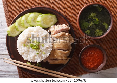 Hainanese chicken rice close-up on a table, chili sauce and broth. horizontal view from above - stock photo