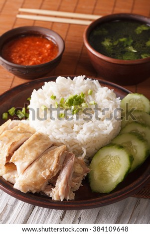 Hainanese chicken rice close-up on a table, chili sauce and broth. vertical - stock photo