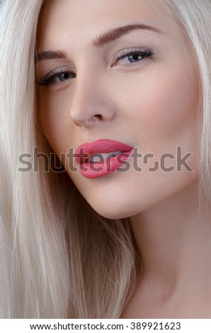 Hair and make-up theme: beautiful young blond woman with creative hair styling with red lips on gray background in studio