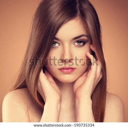 Hair and skin care. Close-up portrait of beautiful sensual young woman touching her pure face.  - stock photo