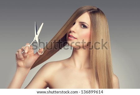 Hair. Beautiful Blonde Girl. Healthy Long Hair. Beauty Model. Scissors - stock photo