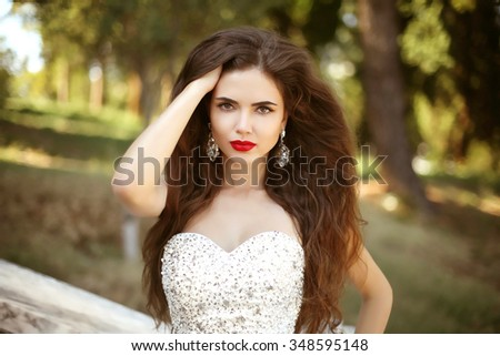 Hair. Beautiful Brunette Girl Bride Model. Red lips makeup. Beauty Fashion woman in luxurious wedding dress posing over park background. - stock photo