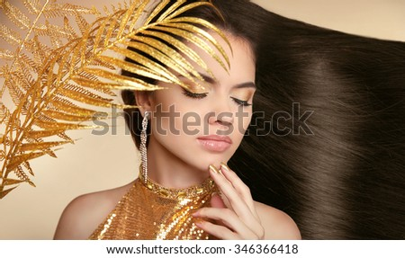 Hair. Beautiful Brunette Girl. Healthy Long glossy Hairstyle. Beauty make-up. Jewelry. Manicured nail. Fashion art photo of young woman isolated on beige background. - stock photo