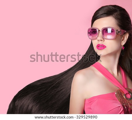 Hair. Beautiful Brunette Girl. Healthy Long Hairstyle. Fashion  sunglasses. Beauty Model Woman. Glamour female person isolated on pink studio background. - stock photo