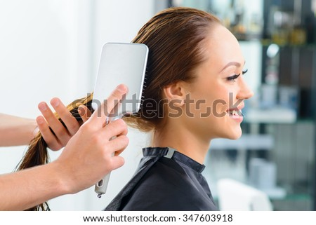 Hair brushing. Young appealing client is smiling while her hair is being brushed by a professional.  - stock photo