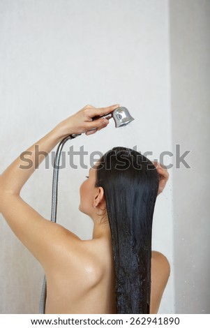 Hair care. Woman in shower washing hair.