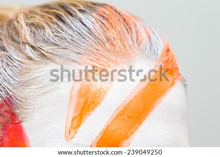 Hair coloring brush, painting hair orange. Makeup artist in the salon hair color model. Creativity, makeup, make-up, hair and face coloring. - stock photo