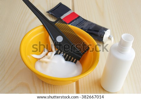 Hair coloring set with hair dye, paintbrush, hairbrush, paint containers on wooden background - stock photo