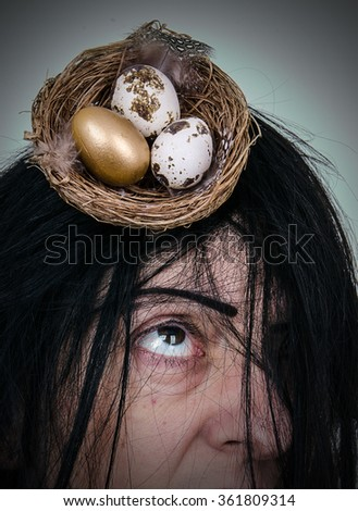 Hair like a bird's nest. Woman with messy hair and a birds nest containing eggs. Close up. - stock photo