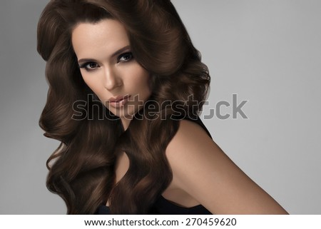 Hair. Portrait of Beautiful Woman with Wavy Hair. High quality image.