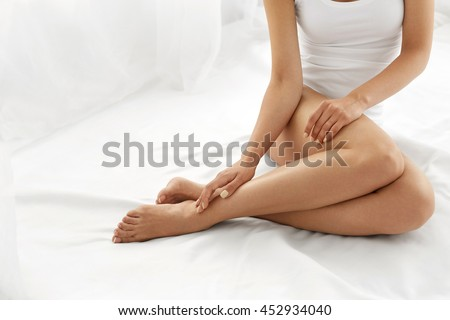 Hair Removal Concept. Closeup Of Beautiful Woman's Hand With Natural Manicure Touching Sexy Long Legs. Young Female Touching Her Perfect Hairless Smooth Soft And Silky Skin. Beauty Body Care Concept