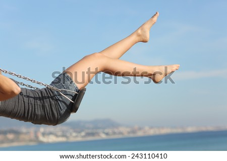 Hair removed woman legs swinging on the beach with the sky in the background - stock photo