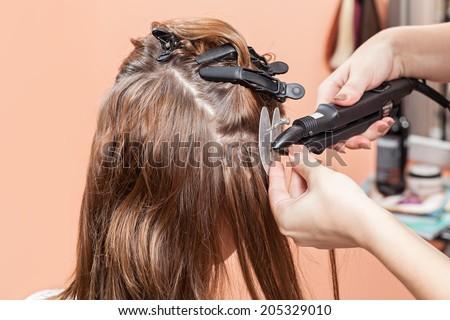 Hair salon, beauty spa. Procedure of hair extensions - stock photo